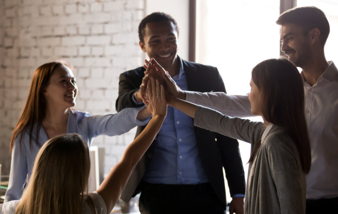 Excited multiracial team give high five