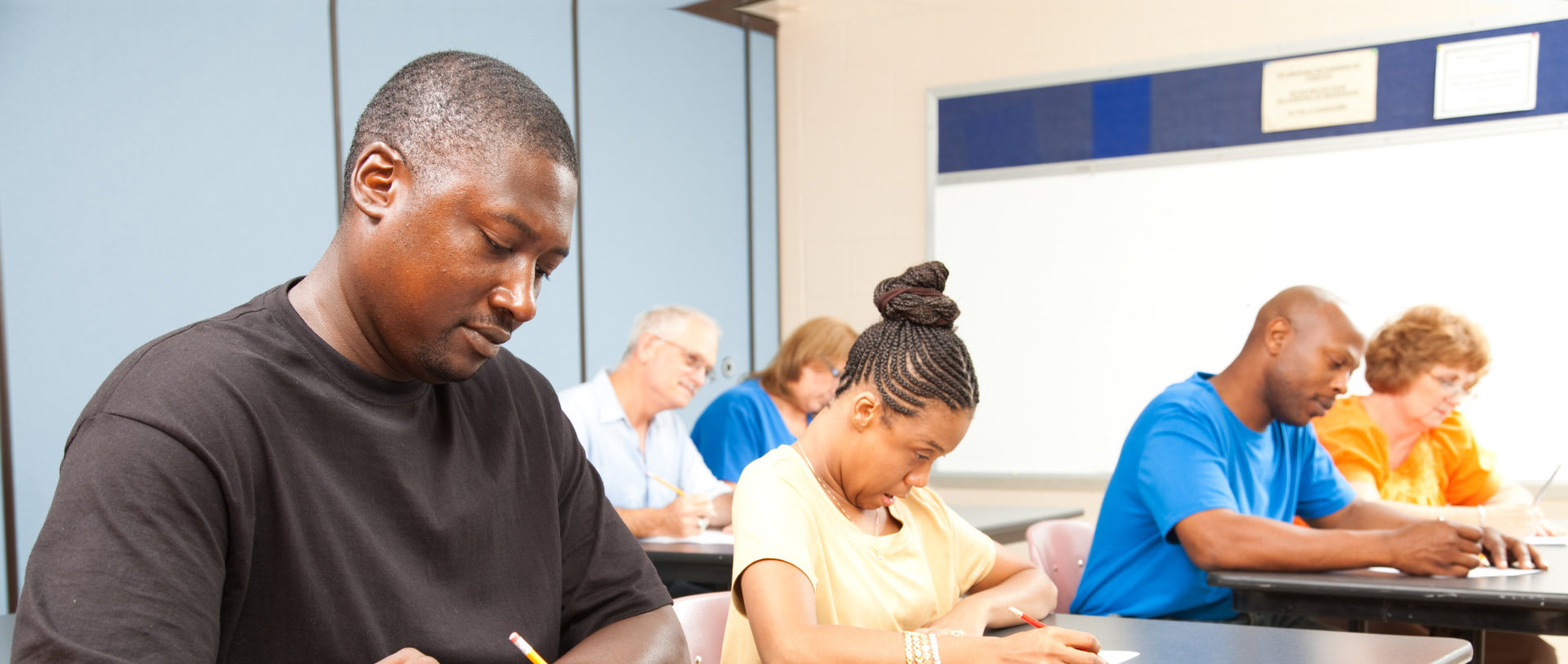 Class of adult college students taking a test